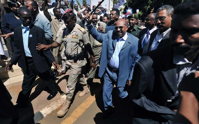 FILE -- Then-President Omar Hassan al-Bashir waves a baton as he arrives at a rally in Khartoum on March 5, 2009. Al-Bashir, ousted in mass protests in 2019, is on trial for his role in the military coup that propelled him to power in 1989. (Lynsey Addario/The New York Times)