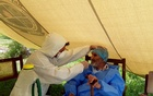 A paramedic wearing protective gear takes a nasal swab of 103 year-old Abdul Alim, to be tested for the coronavirus disease (COVID-19), at the Aga Khan Health Services Emergency Response Centre in Booni, Chitral, Pakistan in this undated photograph provided to Reuters. Suhail Aziz/Handout via REUTERS