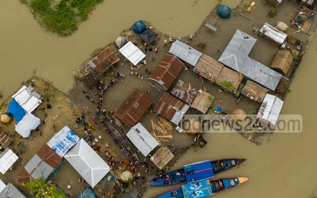 Residents of Nandail Char in Bogura's Sariakandi Upazila wait in a long queue for relief materials. Photo: Mostafigur Rahman