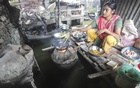 A woman cooks food on a loft as days of heavy rain have left their kitchen submerged. Photo: Asif Mahmud Ove