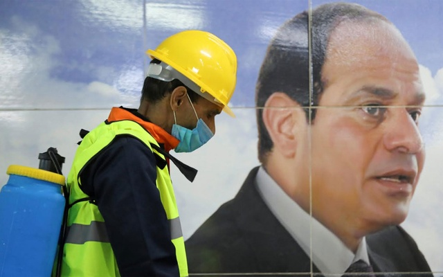 A member of a medical team is seen beside a banner for Egyptian President Abdel Fattah el-Sisi, as he sprays disinfectant as a precautionary move amid concerns over the coronavirus disease outbreak in Cairo on Mar 22, 2020. REUTERS