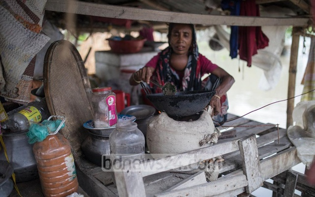Alepa Begum, a resident of Kuripara village in Bogura's Sariakandi Upazila, has taken shelter at a small hut next to a barn after her house went under water.