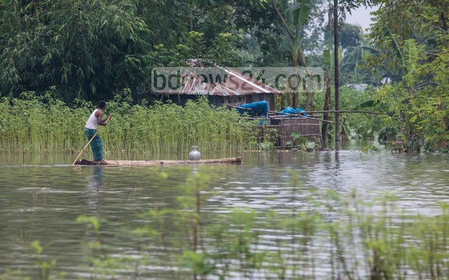 A man collecting drinking water through a makeshift raft as tube wells have are inundated by flash floods in Kuripara village in Bogura's Sariakandi Upazila. Photo: Mostafigur Rahman