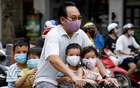 A man and his children, all wearing protective masks, ride a bicycle on a street during the coronavirus disease (COVID-19) outbreak, in Hanoi, Vietnam July 27, 2020. Reuters