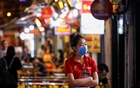 A beer brand promoter wearing a protective mask is seen as she waits for customers in front of a bar, amid the coronavirus disease (COVID-19) outbreak, at Ta Hien night street in Hanoi, Vietnam July 30, 2020. REUTERS