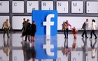 A 3D printed Facebook logo is placed between small toy people figures in front of a keyboard in this illustration taken April 12, 2020. REUTERS