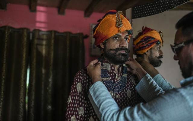 Prince Manvendra Singh Gohi, left, whose family once ruled the kingdom of Rajpipla, is dressed by his husband deAndre Richardson, at their home in Gujarat, India, July 28, 2020. Since coming out as gay in a 2006 interview, Prince Manvendra was disinherited for a time and even burned in effigy. But he has also earned global accolades for his LGBTQ advocacy. (Atul Loke/The New York Times).