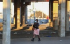 FILE PHOTO: A Stranded commuter walks at a deserted Baragwanath taxi rank during a protest by the South African minibus taxi operators against the government's financial relief package to the taxi industry, during the coronavirus disease (COVID-19) lockdown, in Soweto, South Africa, June 22, 2020. REUTERS