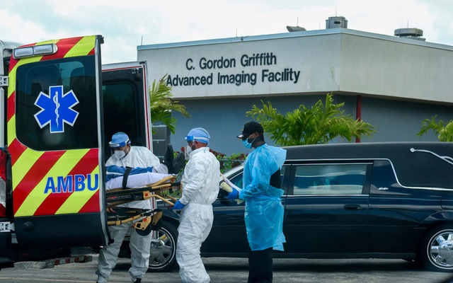 Emergency Medical Technicians (EMT) arrive with a patient while a funeral car begins to depart at North Shore Medical Centre where coronavirus disease (COVID-19) patients are treated, in Miami, Florida, US July 14, 2020. REUTERS