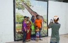Visitors take photographs in front of a mural on the wall adjacent to the entrance of Bangladesh National Zoo in Mirpur. The zoo was closed during Eid-ul-Azha holidays due to the coronavirus epidemic. Photo: Asif Mahmud Ove