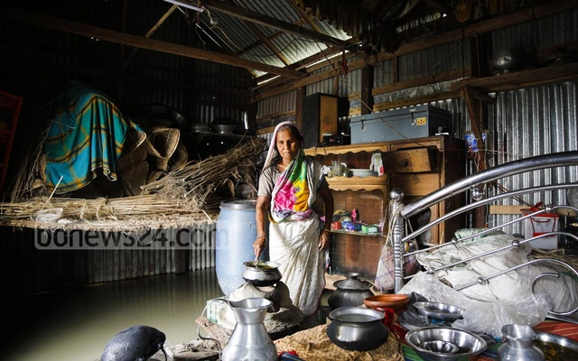 Water has flooded Shamsunnahar's room. She has made a makeshift high base and put her stove on it where she cooks for her son, the only family member.