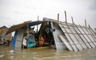 With her house submerged, Ojifa Moni, a resident of Bejgaon Union in Louhjong Upazila, has removed its door. Photo: Mahmud Zaman Ovi