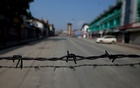 Barbed wire is seen laid on a deserted road during restrictions in Srinagar, August 5, 2019. REUTERS