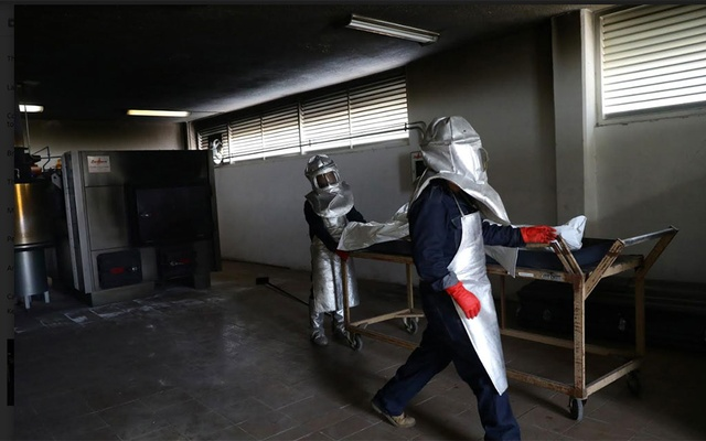 Crematory workers are pictured next to a body bag containing the body of Lorenzo who died of the coronavirus disease (COVID-19) at a crematory in Mexico City in Mexico, August 2, 2020. REUTERS
