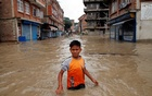 A boy walks along the flooded neighbourhood after incessant rainfall in Bhaktapur, Nepal Jul 12, 2018. REUTERS