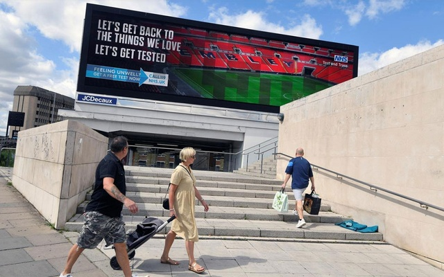 People walk past a British government public health campaign advertisement encouraging people to get tested, amid the spread of the coronavirus disease (COVID-19), in London, Britain, August 2, 2020. REUTERS/Toby Melville