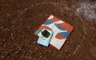 The belongings of a child lie on the ground within a circle drawn with chalk to maintain safe distance, before the start of a class to be held with pre-recorded lessons, after schools were closed following the coronavirus disease (COVID-19) outbreak, in Dandwal village in the western state of Maharashtra, India, July 23, 2020. REUTERS