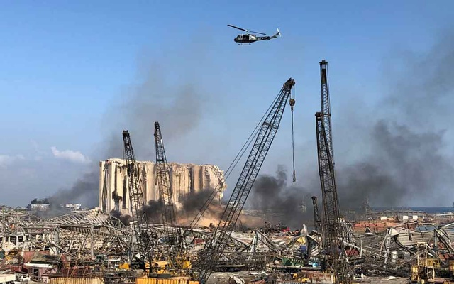A Lebanese army helicopter flies over the site of Tuesday's blast in Beirut's port area, Lebanon, Aug 5, 2020. REUTERS