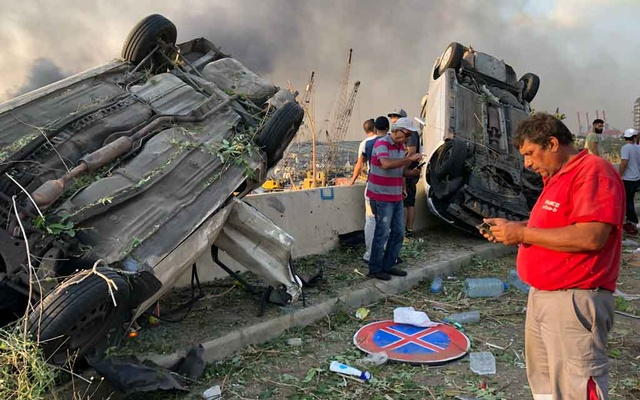 People stand near damaged cars following an explosion in Beirut, Lebanon Aug 4, 2020. REUTERS
