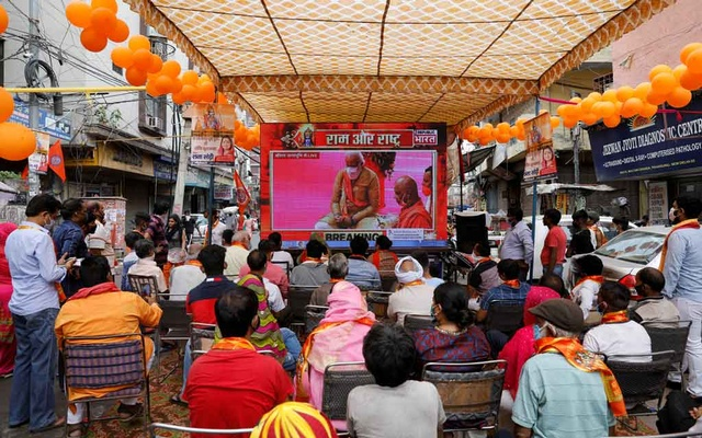 People watch a live screening of the stone laying ceremony of the Ram Temple by Prime Minister Narendra Modi in Ayodhya, in New Delhi, India Aug 5, 2020. REUTERS