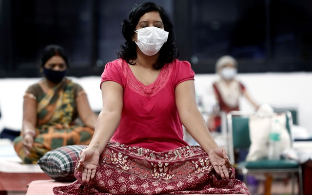 People suffering from the coronavirus disease (COVID-19) perform yoga inside a care centre for patients at an indoor sports complex in New Delhi, India, Jul 21, 2020. REUTERS