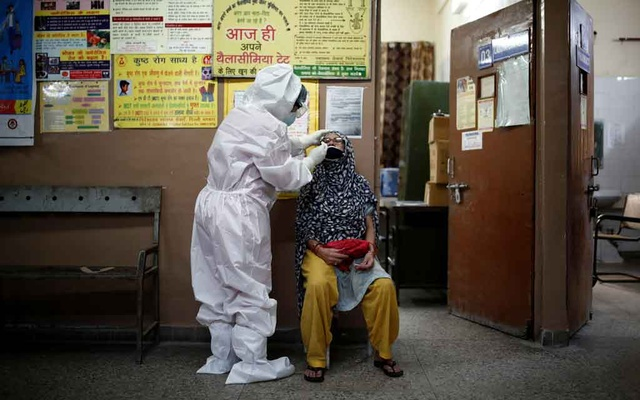 A health worker in personal protective equipment (PPE) collects a sample using a swab from a person at a local health centre to conduct tests for the coronavirus disease (COVID-19) in New Delhi, India August 7, 2020. REUTERS