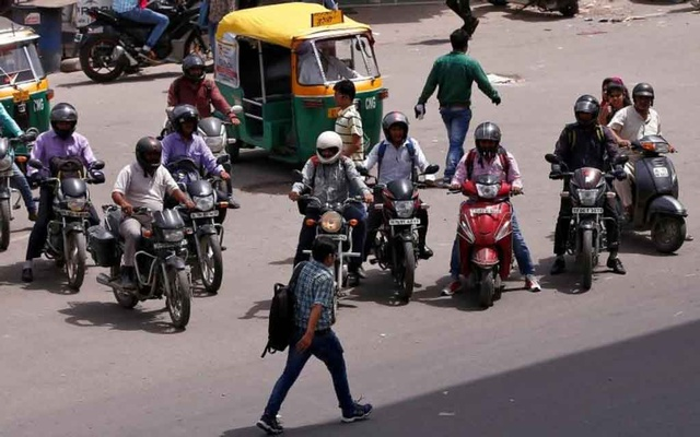 People riding motorcycles wait to cross a road at a traffic signal in New Delhi, India, Jun 16, 2016. REUTERS/FILE