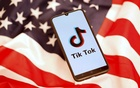 FILE PHOTO: TikTok logo is displayed on the smartphone while standing on the US flag in this illustration picture taken, November 8, 2019. REUTERS