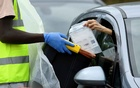 An official collects a testing kit through a car window at a mobile drive through coronavirus disease (COVID-19) testing centre, in Richmond, London, Britain August 4, 2020. Reuters