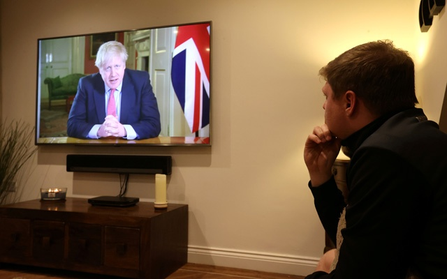 A man watches British Prime Minister Boris Johnson's press conference as the spread of coronavirus disease (COVID-19) continues in Newcastle-under-Lyme, Britain Mar 23, 2020. REUTERS