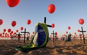 Crosses, balloons and Brazilian flags are seen at Copacabana beach in Rio de Janeiro, placed by members of the NGO Rio de Paz in tribute to the one hundred thousand mortal victims of the coronavirus disease in Brazil on Aug 8, 2020. REUTERS