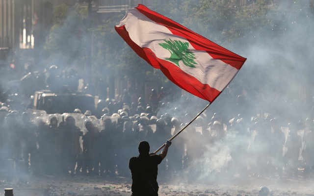 A demonstrator waves the Lebanese flag in front of riot police during a protest in Beirut, Lebanon, August 8, 2020. Reuters