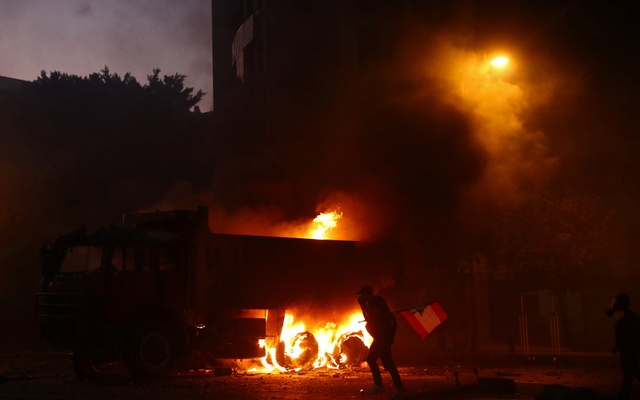 A demonstrator reacts as a truck is seen on fire during a protest following Tuesday's blast, in Beirut, Lebanon August 8, 2020. Reuters