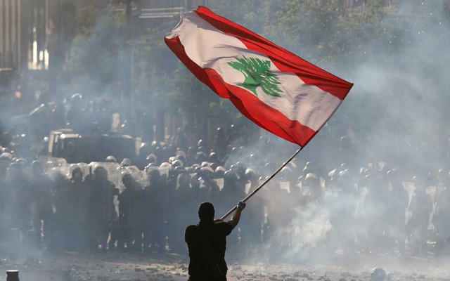 A demonstrator waves the Lebanese flag in front of riot police during a protest in Beirut. Reuters