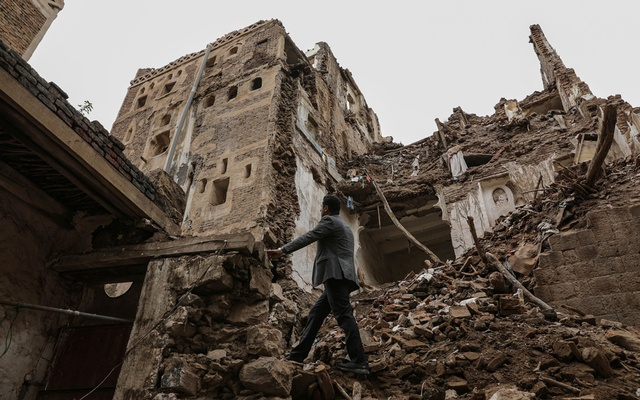 A man walks past a building collapsed by rain in the UNESCO World Heritage site of the old city of Sanaa, Yemen August 8, 2020. REUTERS