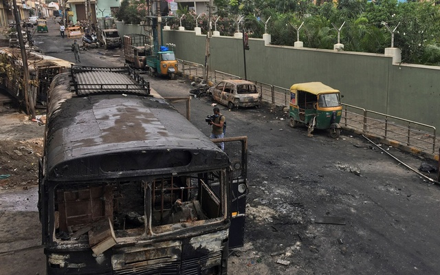 A television news camera operator films burnt police bus and other private vehicles after violence erupted between police and protesters over a reported derogatory Facebook post about Islam's Prophet Mohammad, in Bengaluru, India, August 12, 2020. Reuters