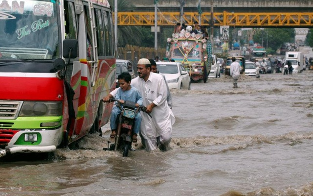 People and vehicles pass through a flooded road after the rain in Karachi, Pakistan Aug 31, 2017. REUTERS/FILE