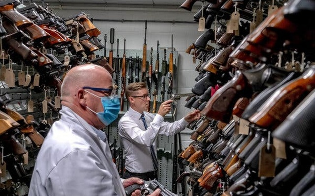 Gregg Taylor, right, at the National Ballistics Intelligence Service in Birmingham, England. Hundreds of illegal guns that officers have seized have come from the United States. Andrew Testa for The New York Times