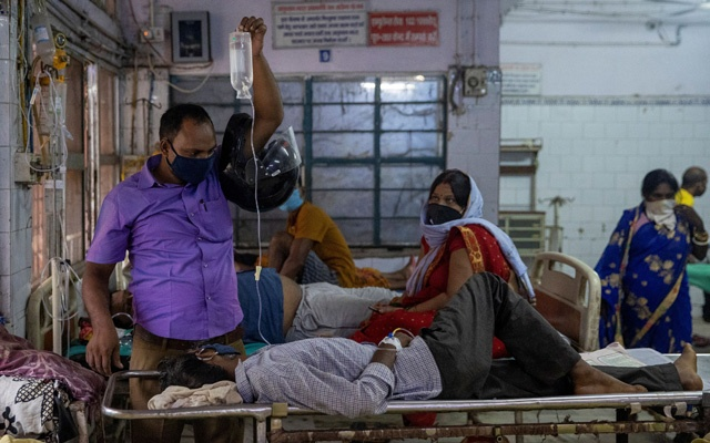 A man holds up an intravenous (IV) drip being used to treat his relative as they wait for him to be transferred to a hospital bed in the emergency ward of Jawahar Lal Nehru Medical College and Hospital, during the coronavirus disease (COVID-19) outbreak, in Bhagalpur, Bihar, India, July 28, 2020. REUTERS