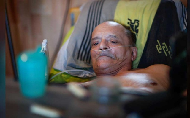 Alain Cocq, 57, in his medical bed he has been confined to for years as a result of a degenerative disease that has no treatment, poses after an interview with Reuters at his home in Dijon, France, Aug 19, 2020. REUTERS