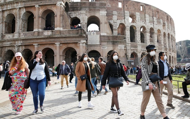 People wearing protective masks walk past the Colosseum in Rome, Italy, February 25, 2020. REUTERS/Remo Casilli