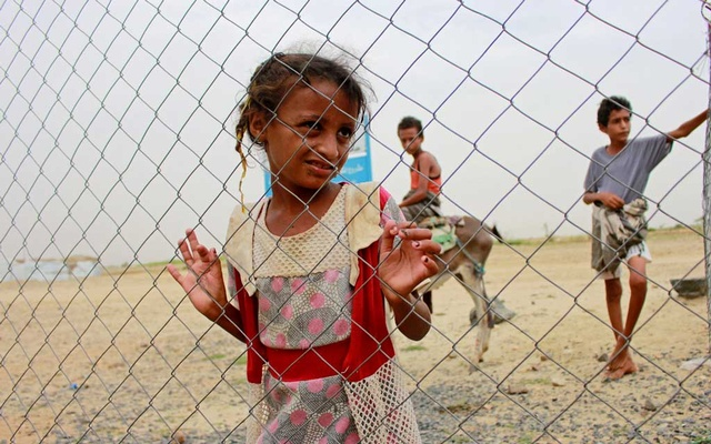 A girl looks through the fence of a closed clinic at a camp for internally displaced people near Abs of Hajjah province, Yemen August 19, 2020. REUTERS