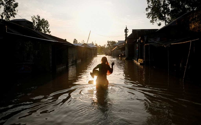 A woman is silhouetted when she walks on a flooded road in Jamalpur. The Asian Development Bank will provide financial assistance for the projects that include health, social protection and climate resilience. REUTERS