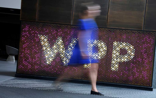 A woman walks past signage for WPP Group, the largest global advertising and public relations agency at their offices in London, Britain, Jul 17, 2019. REUTERS