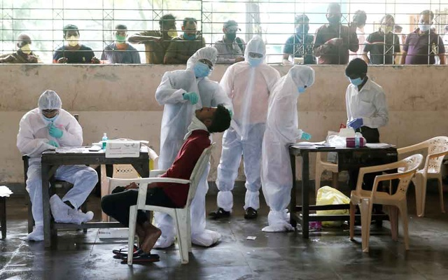 A health worker in personal protective equipment (PPE) collects a swab sample from a man as people outside wait for their test results during a rapid antigen testing check up campaign for the coronavirus disease (COVID-19), at a school in Mumbai, India, August 8, 2020. Reuters