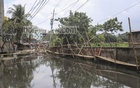Residents of North Bishil in Dhaka's Mirpur have set up a bamboo bridge to cross a street covered with stagnant water from clogged sewrage lines. Photo: Asif Mahmud Ove