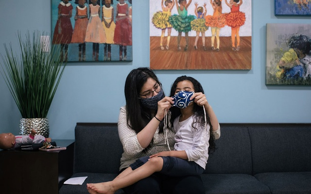 A mother helps her daughter put on a face mask in Hyattsville, Md., April 30, 2020. You may be used to wearing a mask by now, but for many children reentering school, especially those with sensory issues, it can be hard to adjust. (Alyssa Schukar/The New York Times)
