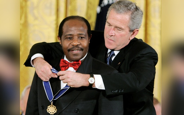 US President George W Bush (R) presents his Presidential Medal of Freedom to Paul Rusesabagina, who sheltered people at a hotel he managed during the 1994 Rwandan genocide, at a ceremony in the East Room of the White House in Washington November 9, 2005. REUTERS