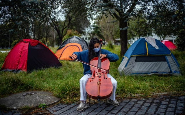 Gabriela Delgado plays cello while participating in a hunger strike, demanding the government to cover their university tuition, in Bogota, Colombia, on Aug 17, 2020. Federico Rios/The New York Times