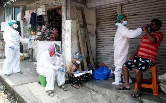 A health worker in personal protective equipment (PPE) rests as her colleagues test residents of a slum area during a check up campaign for the coronavirus disease (COVID-19) in Mumbai, India Sept 5, 2020. REUTERS